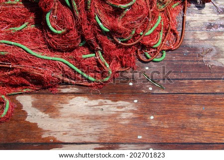 Fishing net on wooden planks - stock photo