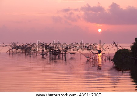 Fishing nets in the lake in Southern part of Thailand in pink warm morning light - stock photo