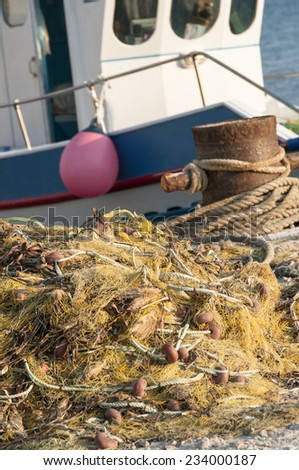 fishing nets piled up on the pier - stock photo