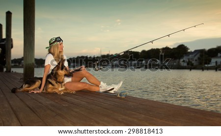 Fishing of the dock with a German Shepard  - stock photo