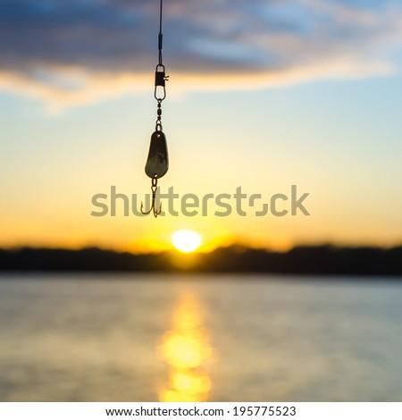 fishing on a lake before sunset - stock photo