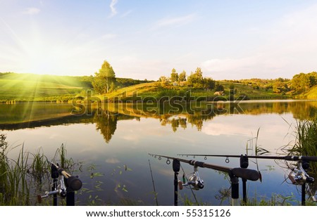fishing on the lake at sunset - stock photo