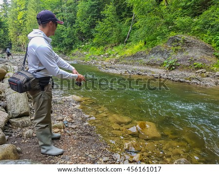 Fishing on the mountain river. Fisherman on the shore. Summer Activities. Fishing - stock photo