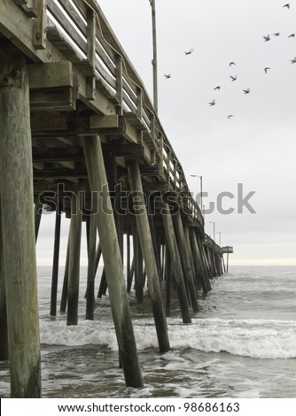 Fishing pier at Virginia Beach, USA, with departing seagulls - stock photo