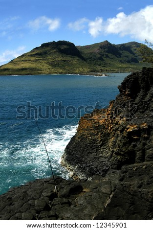 Fishing pole is planted in rocky ledge to catch fish while fisherman is away.  Rocky cliff.  Aqua waters and blue sky. - stock photo