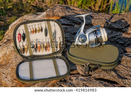 Fishing reel on the natural background. Assorted of various kind of fishing metal baits. Objects on the green box for fishing bait on the old tree with brown bark. - stock photo