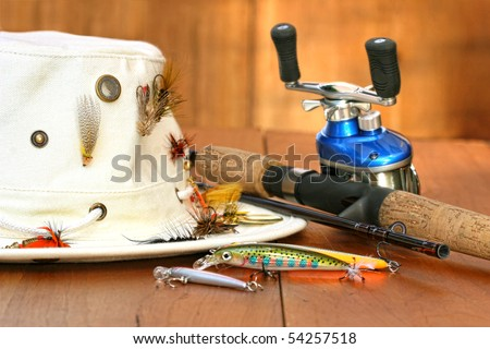 Fishing reel with hat and color lures on wood - stock photo