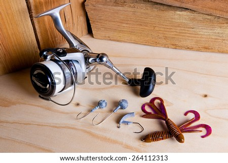 Fishing reel with silicone baits on wooden background. Different tips of the fishing jig baits. - stock photo