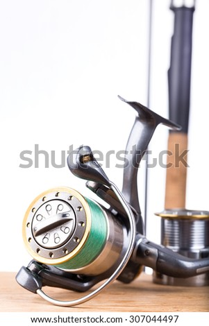 fishing rod and reel with line on white background - stock photo