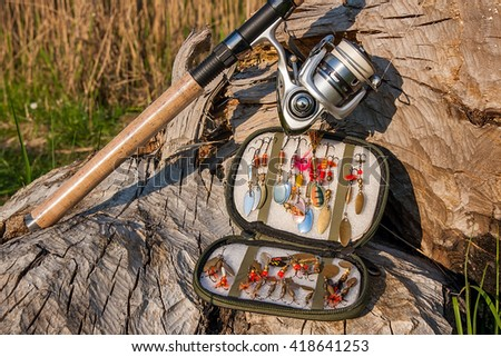 Fishing rod with fishing reel on the natural background. Assorted of various kind of fishing baits. Spinning on the old tree with brown bark. - stock photo