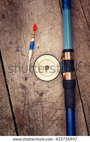 Fishing rod with reel, a float, sinker and hook on a wooden background, retro filter - stock photo