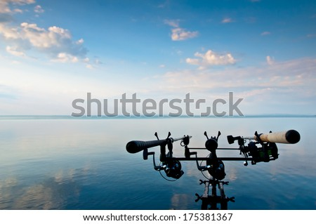 Fishing rods waiting for the fish bites on the lake beach at summer dawn - stock photo