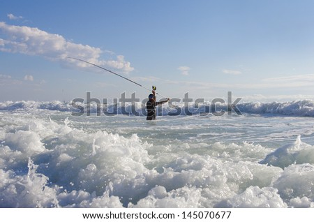 Fishing scene. Surf fisherman into the waves. Atlantic ocean - stock photo