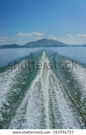 Fishing speedy boat prop wash, white wake on the blue ocean sea - stock photo