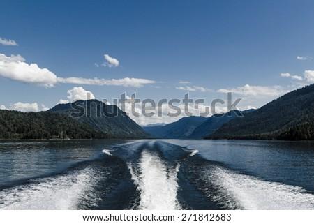 Fishing speedy boat prop wash, white wake on the blue ocean sea - stock photo