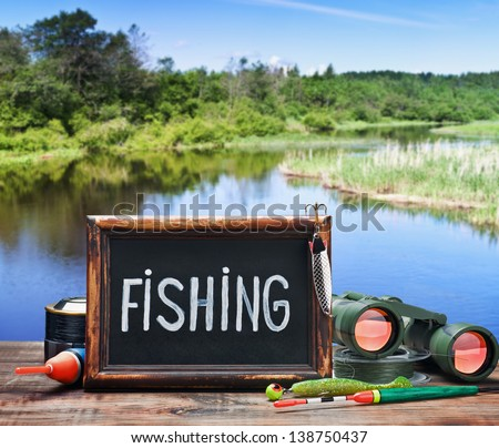 fishing tackle and a blackboard - stock photo