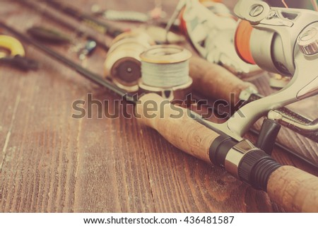 Fishing tackle - fishing spinning, fishing line, hooks and lures on wooden background. Toned image, with place for text - stock photo