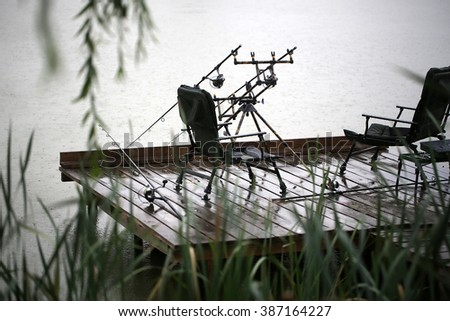 Fishing tackle gear two convertible chairs stay outdoor in rain drops falling plop into water on wet wooden pier over natural rainy day background, horizontal picture - stock photo
