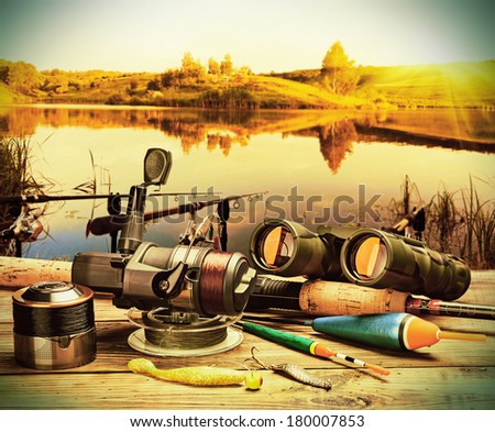 fishing tackle on a pontoon on the background of the lake  - stock photo