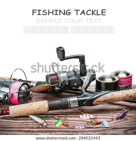 fishing tackle on a wooden table isolated on a white background. Focus on spinning. - stock photo