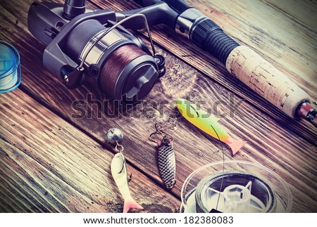 fishing tackle on a wooden table. toned image - stock photo