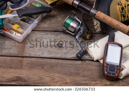 fishing tackles and fishing gear on tinber boards - stock photo
