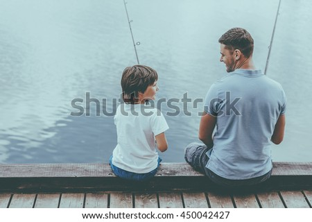 Fishing together is fun. Rear view of father and son fishing while sitting on quayside together - stock photo