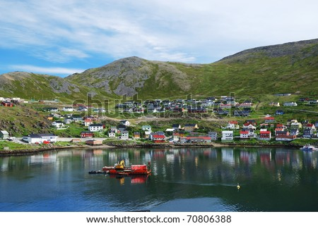 Fishing town is located on the side of blue fjord. Mageroya is photographed in summer. There are wooden houses on the green mossy hills and a lot of blue water. - stock photo