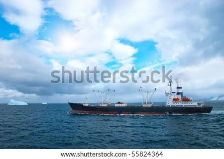 Fishing trawler in Atlantic ocean near icebergs - stock photo