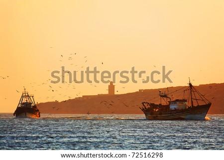 Fishing trawlers in sunset light, Essaouira, Morocco, Africa - stock photo