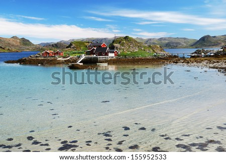 Fishing village is in the small island surrounded with blue fjord during low tide in summer. There are several wooden houses, motorboats, mossy hills and a lot of transparent water. - stock photo