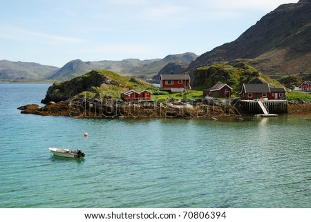 Fishing village is in the small island surrounded with blue fjord. Mageroya is photographed in summer. There are several wooden houses, motorboats, mossy hills and a lot of transparent water. - stock photo