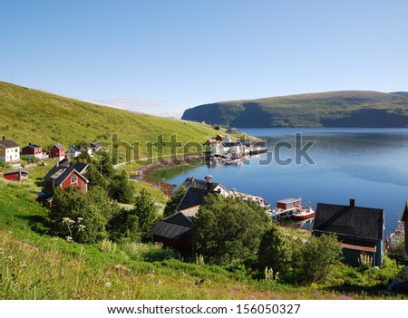 Fishing village is located on the side of blue fjord. Soroya is photographed in summer. There are wooden houses on the green mossy hills and a lot of blue water. - stock photo