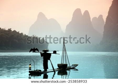 Fishing with cormorants birds in Yangshuo, Guangxi region, traditional fishing use trained cormorants to fishi, China - stock photo