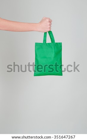 Fist holding a green textile bag -  ecological shopping concept - stock photo