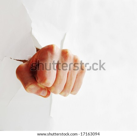 Fist punching through paper creating a torn hole - stock photo