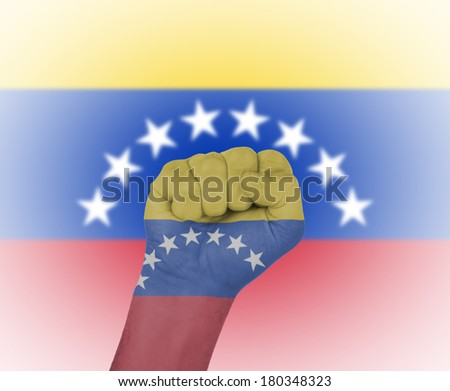 Fist wrapped in the flag of Venezuela and flag in the background - stock photo