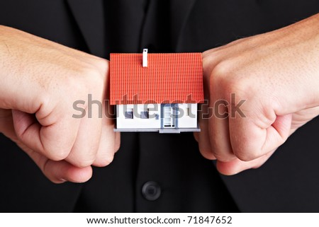 Fists pressing from two sides against a small house - stock photo
