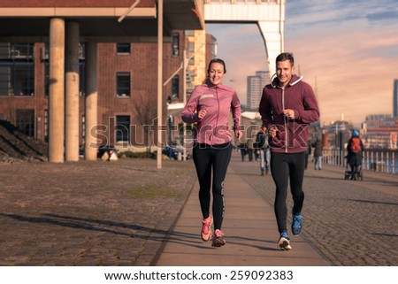 Fit active young couple running on a seafront promenade with the athletic woman leading the way approaching the camera in a healthy lifestyle concept - stock photo
