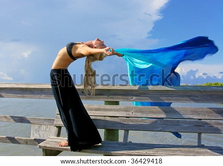 fit and attractive blonde woman is arching back making her arms horizontal as the wind blows back her veil - stock photo