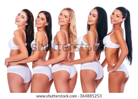 Fit and curvy. Group of beautiful women in lingerie looking over their shoulders and smiling while bonding to each other and standing in a row against white background - stock photo