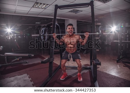 Fit and strong man doing squats in the gym. - stock photo