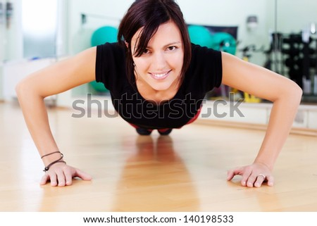 Fit athletic young woman doing press-ups at the gym on a hardwood floor facing the camera with her head raised looking at the camera with a smile - stock photo