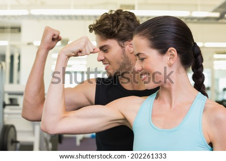 Fit attractive couple comparing biceps at the gym - stock photo