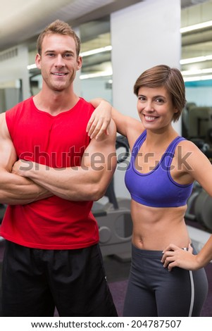 Fit attractive couple smiling at camera at the gym - stock photo