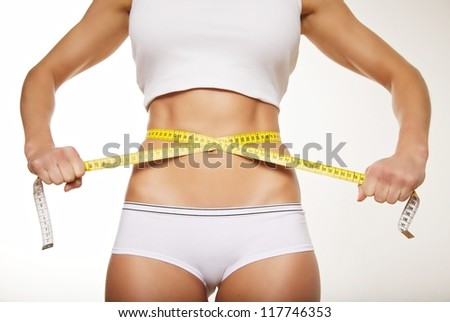 Fit beautiful woman holding measure tape around her stomach. Weight loss concept. - stock photo