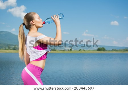 Fit beautiful young blonde Caucasian woman drinking water after workout by the sea. Teenage runner at the beach with bottle of water refreshing after workout. Fitness, diet,active lifestyle concept. - stock photo