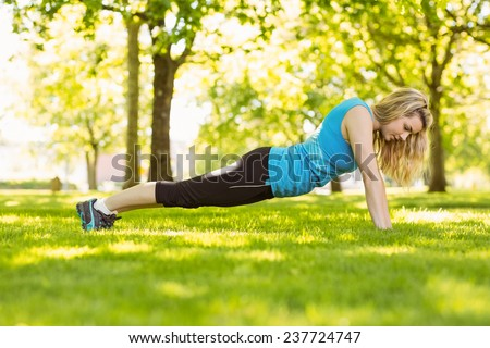 Fit blonde doing push ups in the park on a sunny day - stock photo