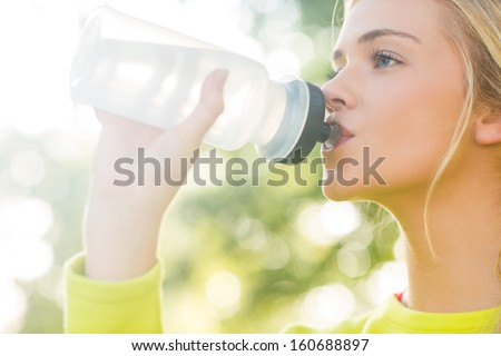 Fit blonde drinking from sports bottle in a park on a sunny day - stock photo