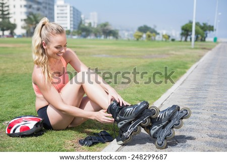 Fit blonde getting ready to roller blade on a sunny day - stock photo